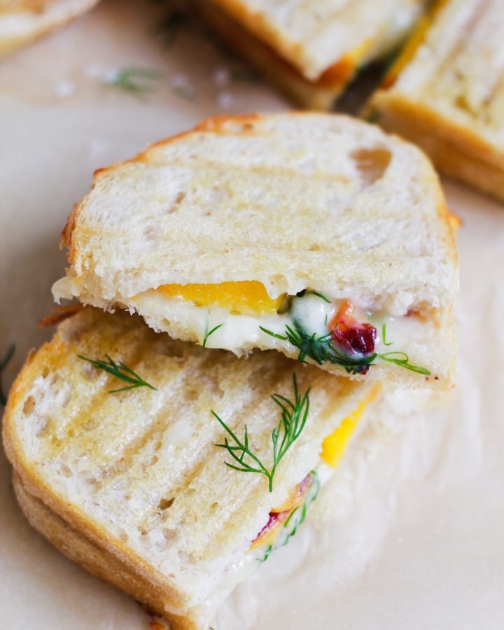 sliced healthy grilled cheese sandwich with peach and dill