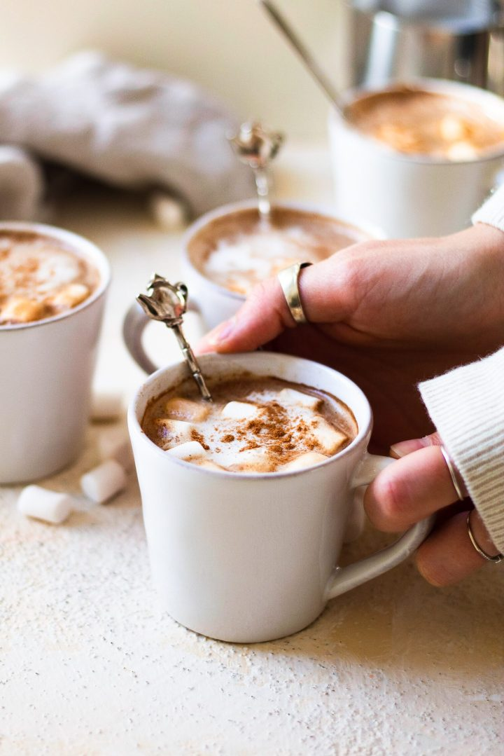 hands holding hot cocoa espresso drink