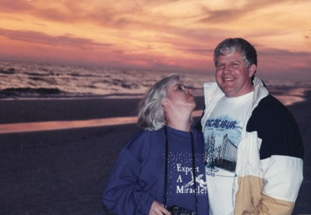 woman and man standing on beach at sunset