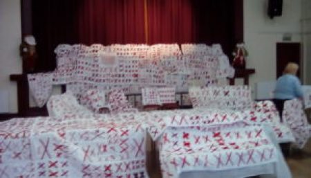 quilts of all sizes, each with a white base adorned with pairs of red X's are draped over chairs and tables at Coxhoe Village Hall in the U.K.