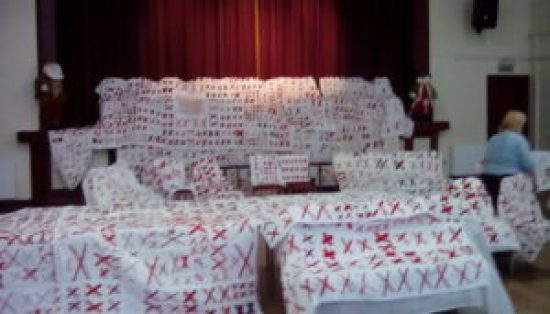 White quilts covered with pairs of red X's draped over church pews and chairs