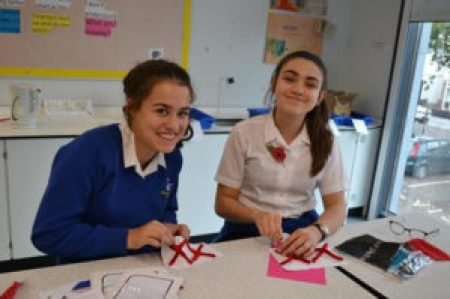 A female teenager wearing a blue sweater sits beside a female teenage student stitching pairs of red X's onto white bases to commemorate some of the 70273 disabled people who were murdered by Nazis