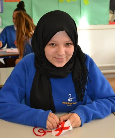 A female student of the Waldegrave School stitches two red X's on a white base to make a block for The 70273 Project