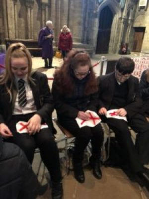 students stitch pairs of red X's onto white cloth to commemorate one disabled person murdered under Aktion T4