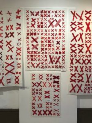 quilts made of pairs of red X's stitched to white background fabric