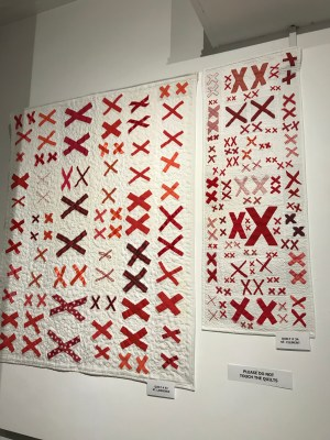 quilts made of pairs of red X's stitched to white background fabric hanging on a wall
