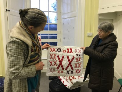 2 women hold a small quilt made of pairs of red X's stitched to a white background