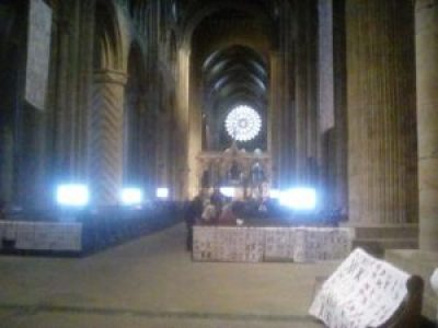 quilts made of pairs of red X's sewn onto white background fabric are displayed in Durham Cathedral in the U.K.