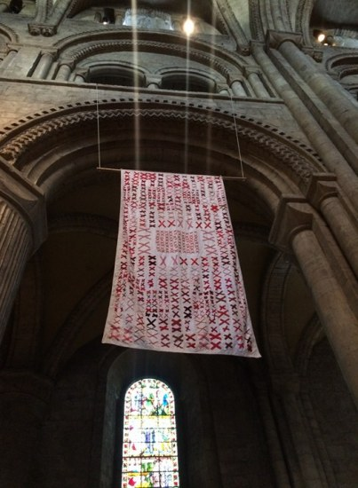 A quilt with a white background covered in pairs of red X's hanging high in an ancient cathedral