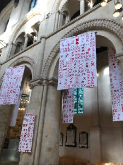 White quilts covered with pairs of red X's hang in an ancient cathedral