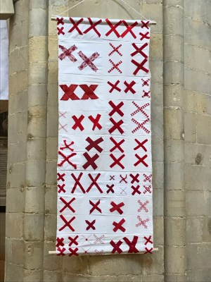 a quilt made of pairs of red X's sewn onto a white background