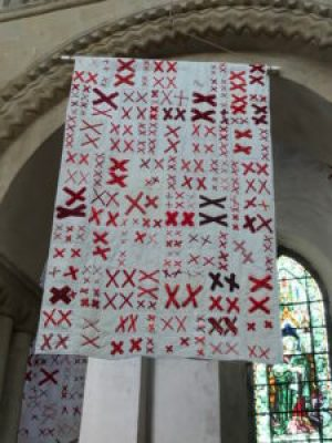 a quilt made of pairs of red X's stitched to a white background