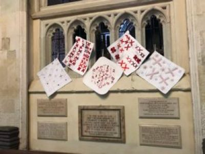small quilts made of pairs of red X's sewn onto a white background fabric