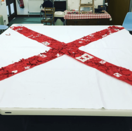 a large red x is stitched onto the white cloth background