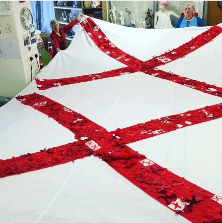Two red X's are stitched onto a large white cloth background as women look on