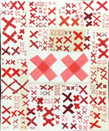 white and off white quilt base covered with pairs of red X's