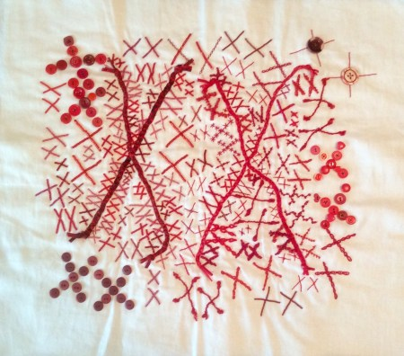 white quilt with pairs of red Xs