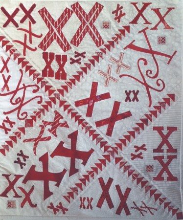 a white quilt with pairs of red X's