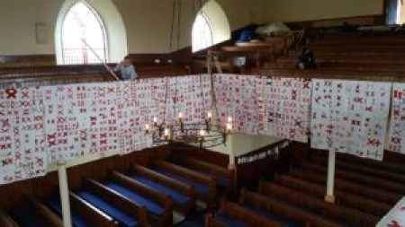 many white quilts covered with pairs of red X's hang from the balcony at the Priory in Whithorn, Scotland