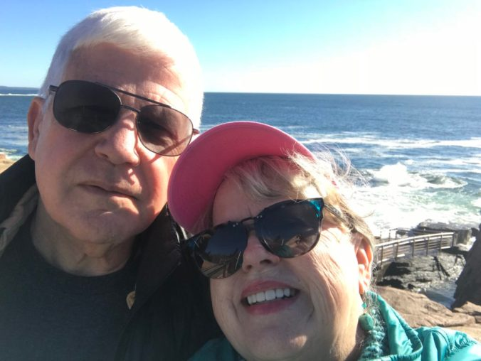 white haired man stands beside woman in pink hat in front of the ocean