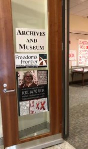 open door covered with signage about the Archives and Museum and the exhibit