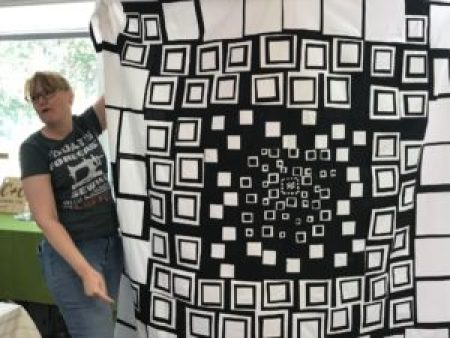 woman holds up a black and white quilt