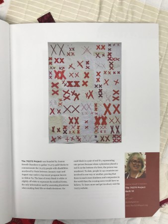 a page in a magazine containing a photo of and an article about Quilt #10 of The 70273 Project. The quilt is a rectangular white quilt covered with pairs of red X's.