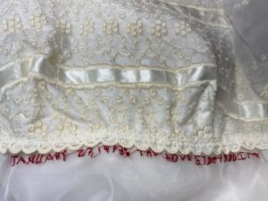 Red text embroidered on wedding dress