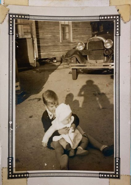 a boy holding a baby in front of an old car parked beside an unpainted house