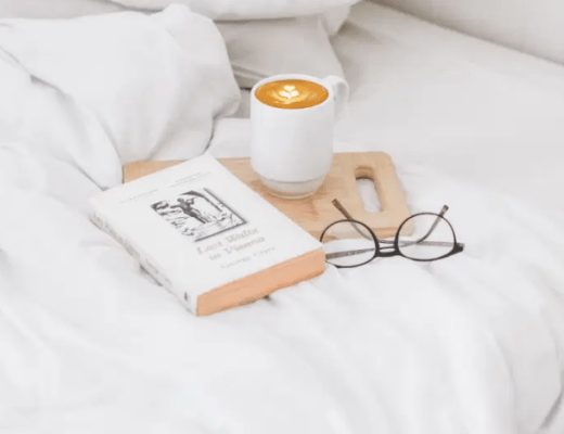 A styled bed with a cup of coffee, glasses and a book on the BDC Collective by BDC Digital Media both by Brenda Della Casa