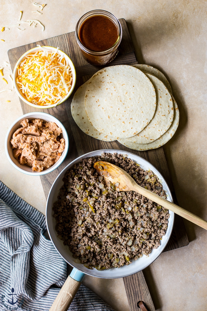 Overhead photo of ground beef mixtire in skillet, tortillas, shredded cheese and refried beans in bowls