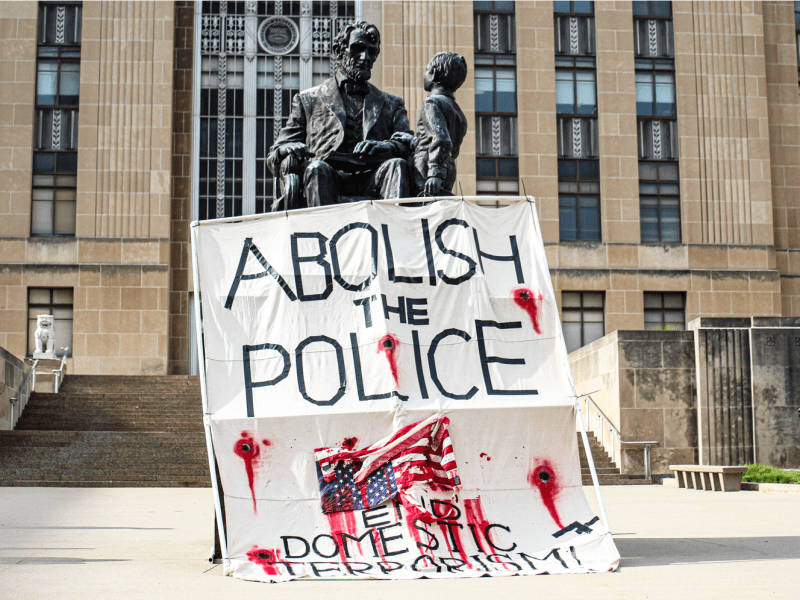 Members of One Struggle KC draped a banner over the statue of Abraham Lincoln during a demonstration outside of city hall on June 8, 2020. (Zachary Linhares/The Beacon)
