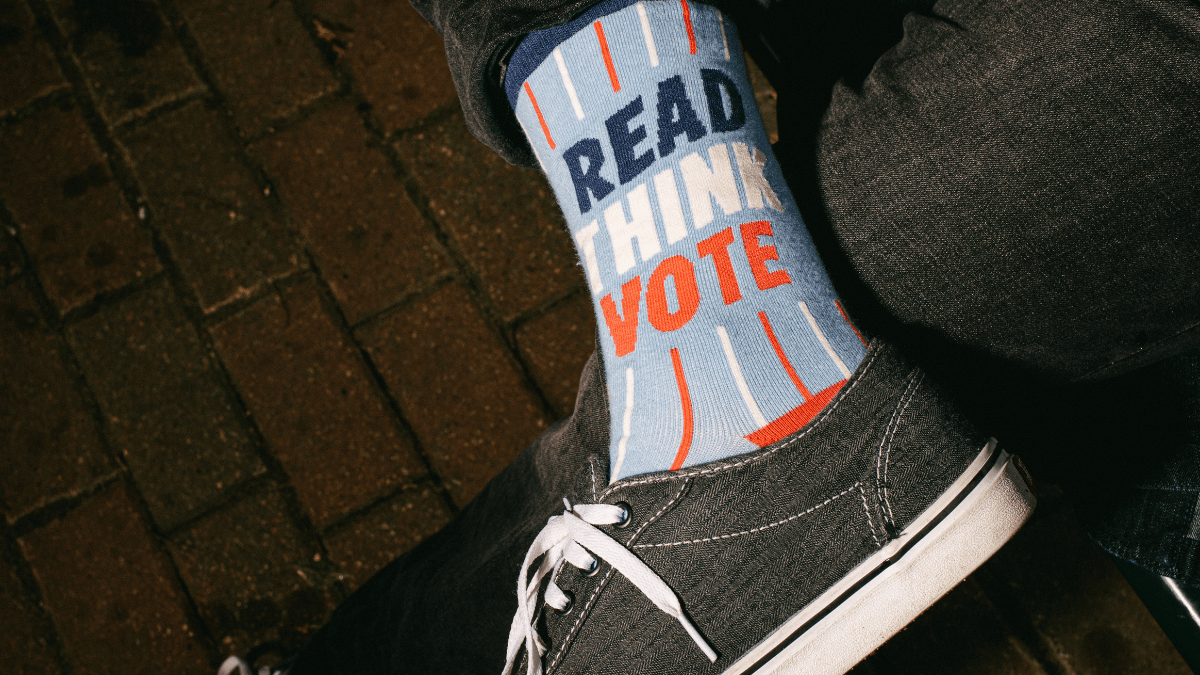 """Baker University student Will Hanson wears a sock that says """"Read, think, vote."""" This year will be his first time voting in a presidential election. (Zach Bauman/The Beacon)"""