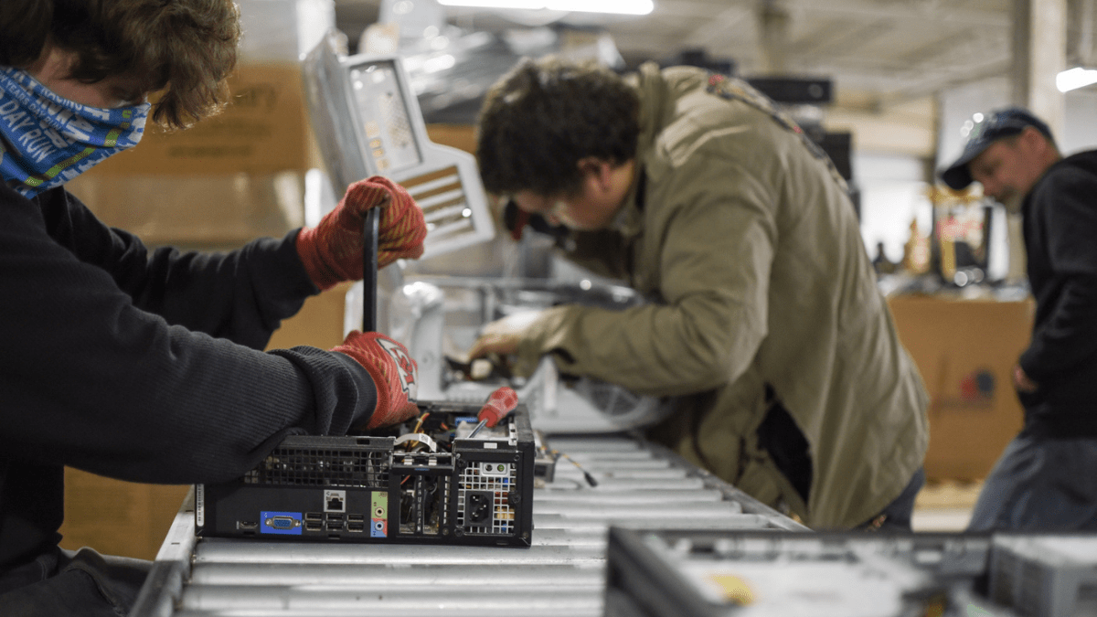 Two people take apart desktop computers, which will then be refurbished and sold at a lower cost to families who need devices in Kansas City.