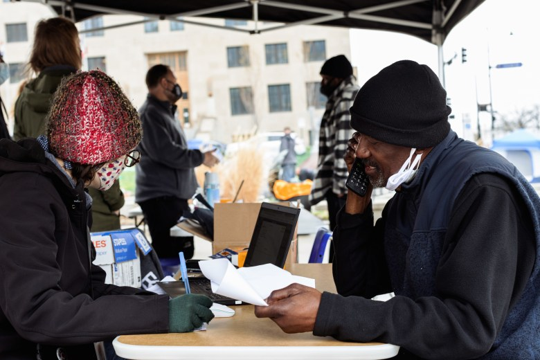 A case manager helps an unhoused man, Raymond Denson, apply for an ID.