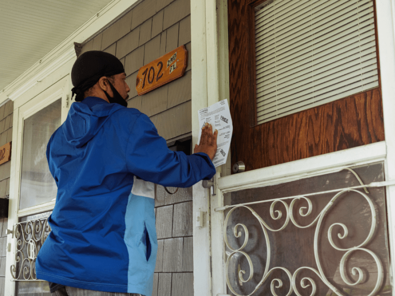 Lamon Lewis places a flyer with vaccine information on a home near downtown Kansas City, Kansas, on May 21, 2021. Photo by Chase Castor/The Beacon