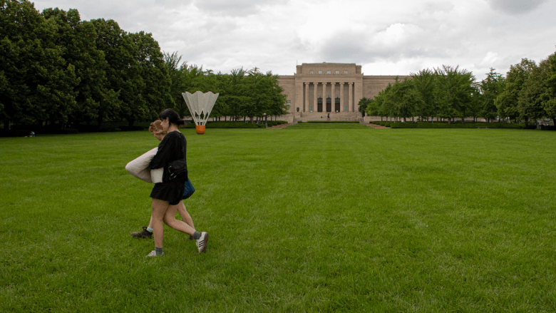Two people walk across the grass in Donald J. Hall Sculpture Park in front of The Nelson-Atkins Museum of Art.