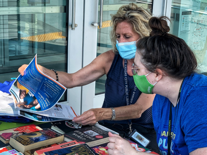 Library employees Kelly Barry and Megan McNaughton flip through one of the informational packets offered at the pop-up.