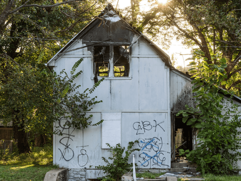 The burned and abandoned property at 2415 Kensington Ave. in Kansas City, MO has graffiti covering the property. Much of the roof is missing or scorched, and fire damage can be seen throughout the home.