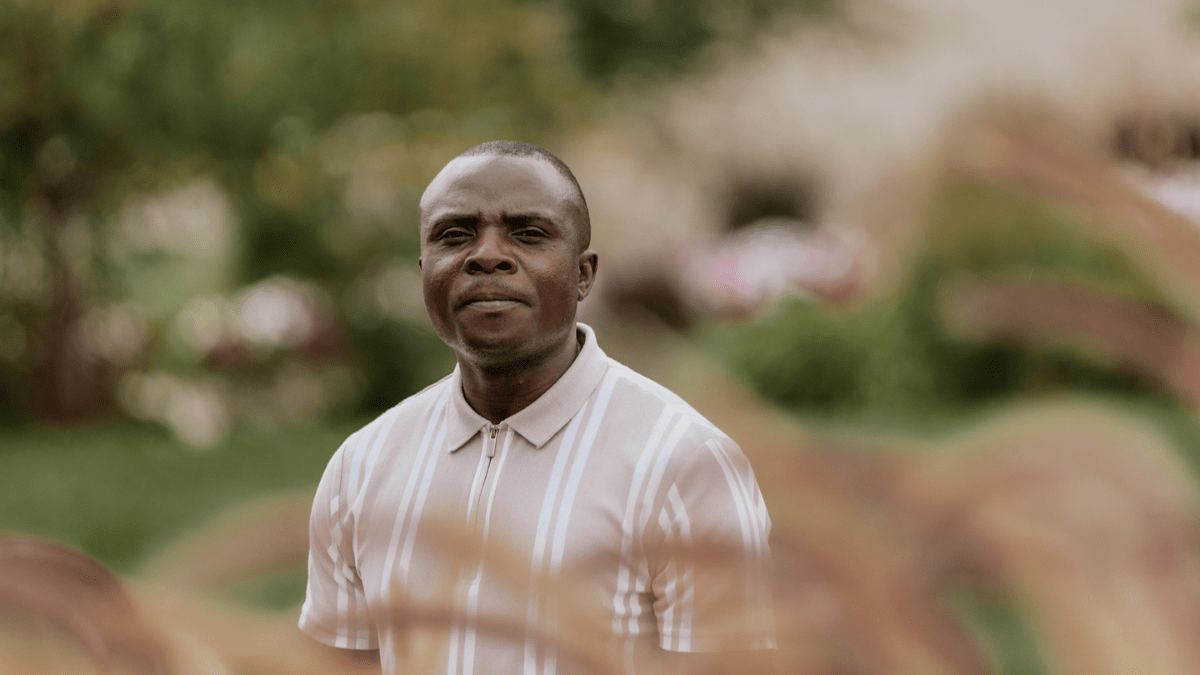 Solomon Kasongo stands in front of a beige building, with trees and grass behind him and wild grass in front of him.
