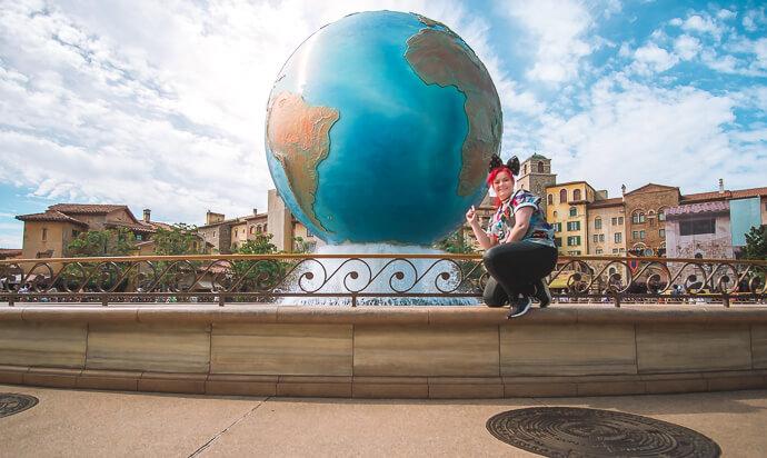 Amelia crouching on ledge in front of Globe fountain - Tokyo Disney Sea