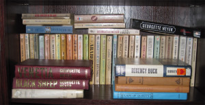 Shelf of books with paperbacks at the back, standing, with some hard back books on their sides in the front.