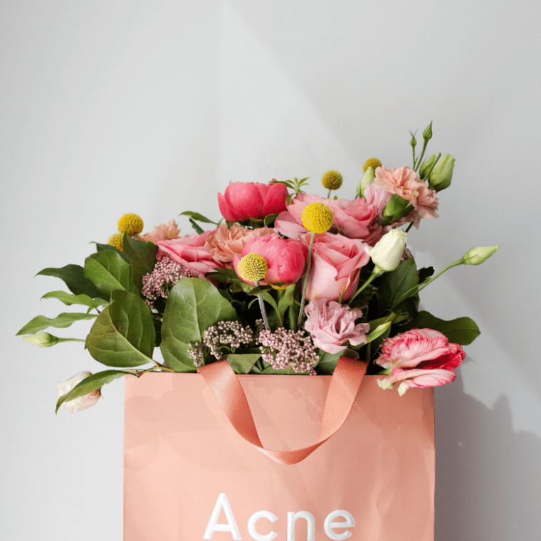 a bag that says Acne and it's full of blooming flowers