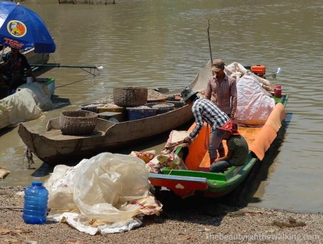 Les pêcheurs débarquent de leur bateaux des paniers remplis de poissons. Lac Tonlé Sap, Kampong Khleang, Cambodge