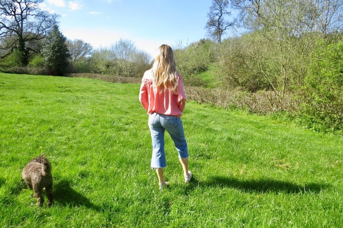 Samantha walking in a field with her dog