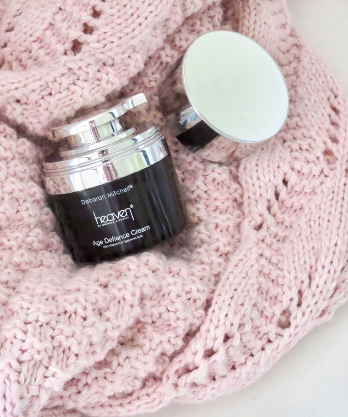image shows the pot of Age Defiance cream placed on a pale pink blanket.