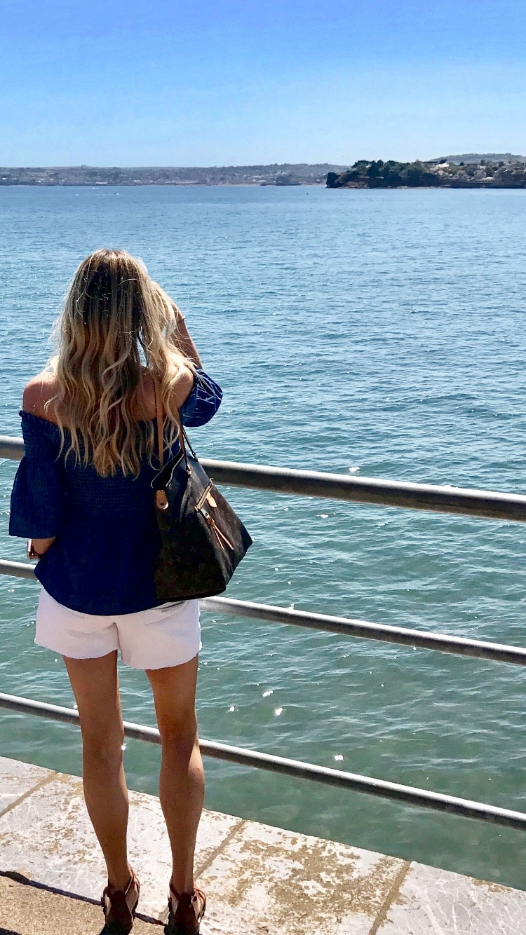 Image shows Samantha looking out to sea wearing white shorts and off shoulder denim top. The white edit.