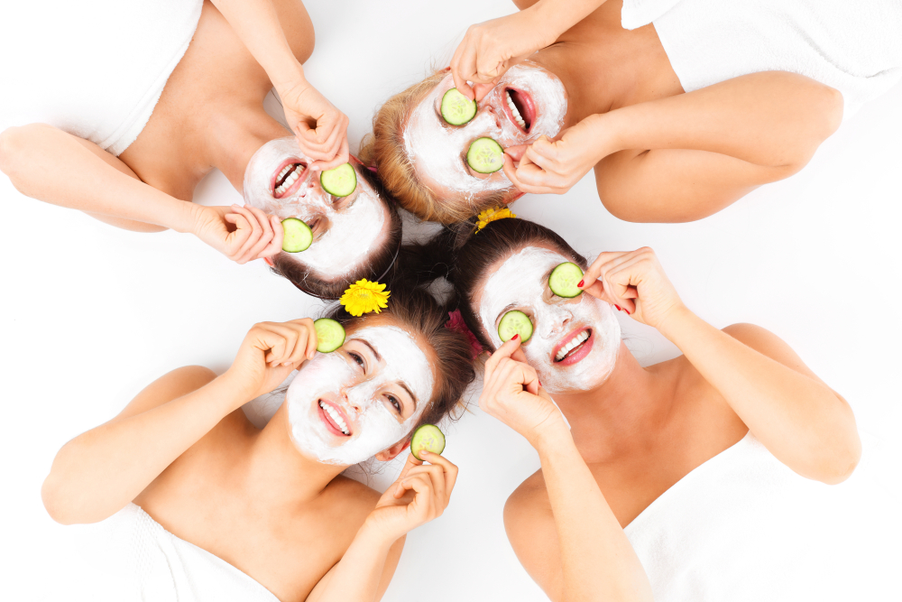 A picture of four friends enjoying their time in spa with facial masks over white background
