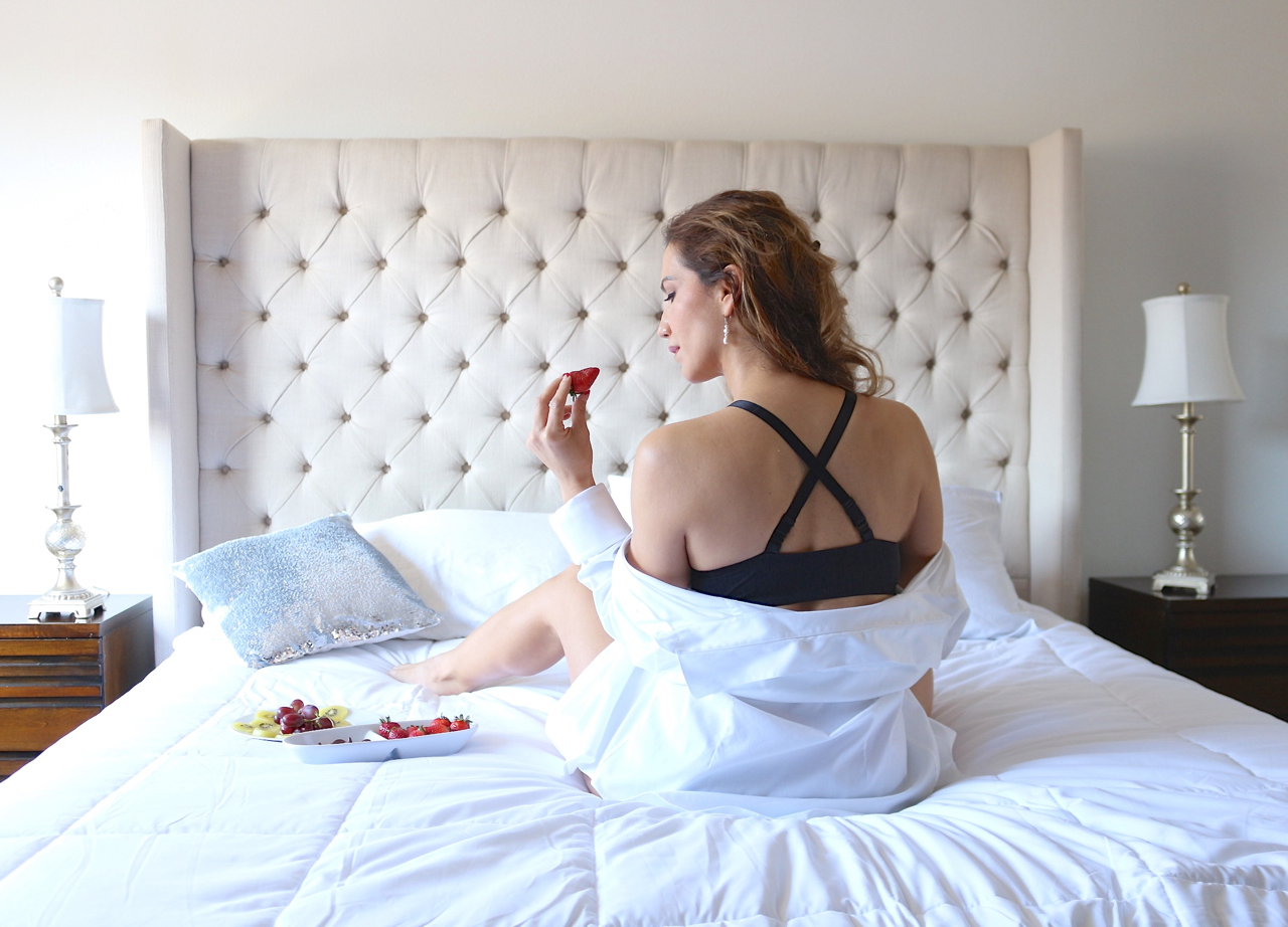 woman sitting on the bed enjoying breakfast