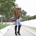 woman wearing a faux fur coat paired with jeans and over the knee boots.